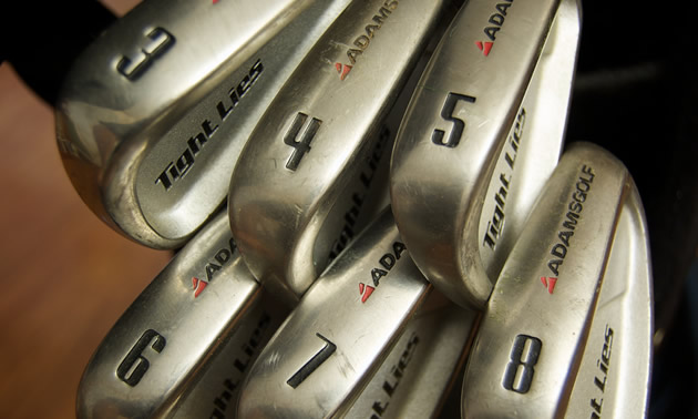 A beginner's set of Adams Tight Lie golf clubs.