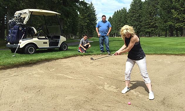 Nicole Lind swinging a golf club trying to get her golf ball out of a sand trap while Eric Buckley and Will Buckley stand next to a golf cart at Cranbrook Golf Club