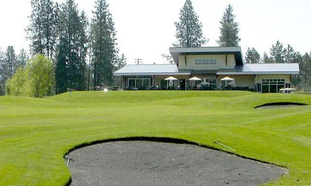 Sand trap in foreground, with clubhouse building in background.