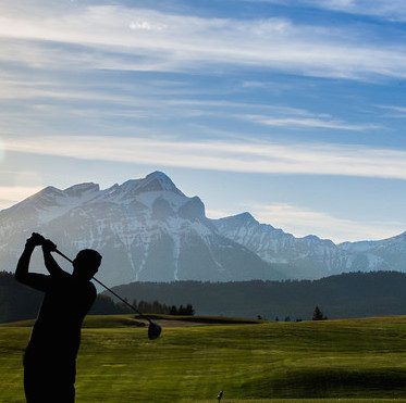 A golfer playing the 17th tee box, silhouetted in soft light, with the mountains blue in the background