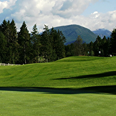 Fairway at River Crossing golf with mountains in the background.