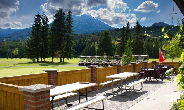 Photo from the clubhouse patio overlooking the course. There are golf carts parked in the foreground and a mountain in the background.