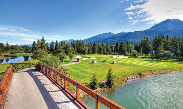 Wooden bridge over stream, with golf course in background.
