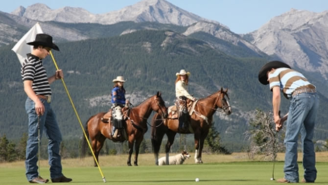 Cowboy golfing with horses and mountains in the background.