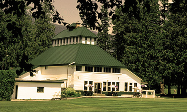 Clubhouse building, white with sloping green roof.