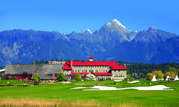 Golf course in foreground, with St. Eugene Resort in background with red roof, and in far distance, towering mountains.