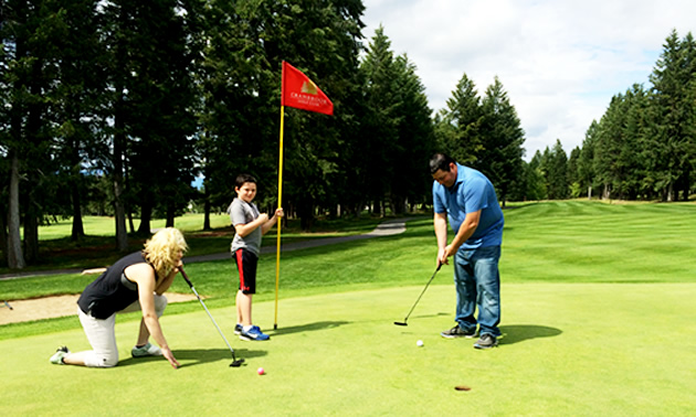 Nicole Lind, Eric Buckley and Will Buckley on the green next to a red flag at Cranbrook Golf Club watching Will putt his golf ball into the hole