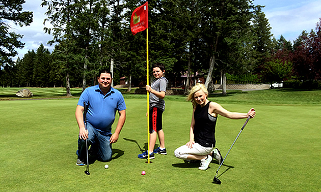 Will Buckley, Eric Buckley and Nicole Lind posing next to a red flag on the golf course at Cranbrook Golf Club