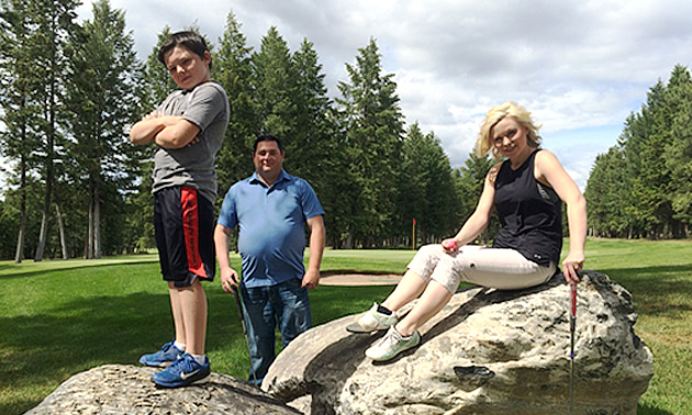 Eric Buckley is standing and Nicole Lind is sitting on rocks while Will Buckley is standing on grass at Cranbrook Golf Club