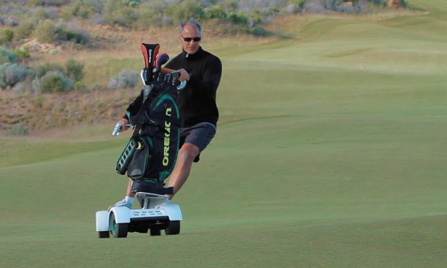 A golfer is riding his GolfBoard on the golf course.